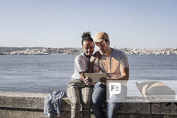 Young couple sitting on a wall at the waterfront using a tablet  Lisbon  Portugal