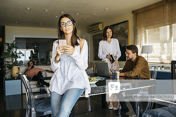 Portrait of woman with cell phone and friends working in background at home