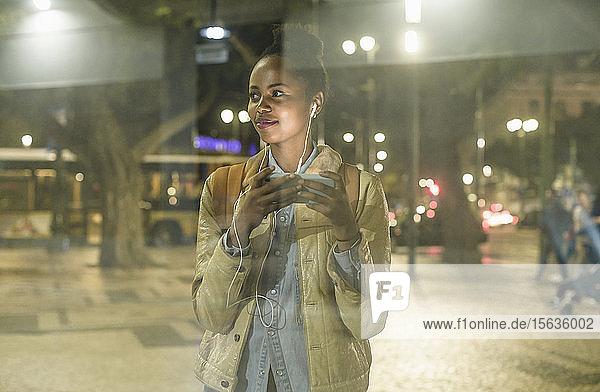 Porträt einer lächelnden jungen Frau mit Smartphone und Kopfhörern  die etwas beobachtet  Lissabon  Portugal