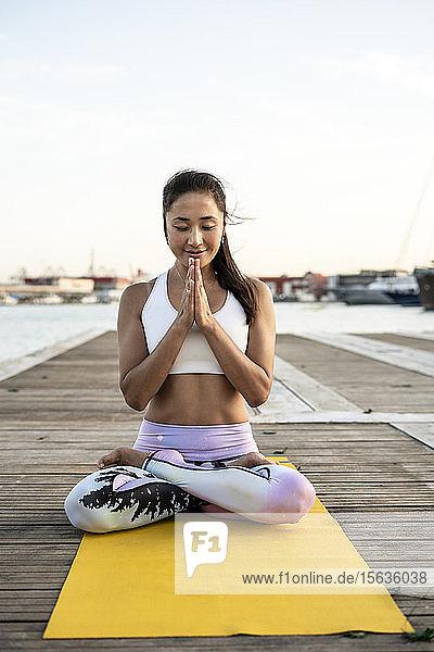 Asiatische Frau  die auf einem Pier im Hafen Yoga praktiziert und meditiert Asiatische Frau, die auf einem Pier im Hafen Yoga praktiziert und meditiert