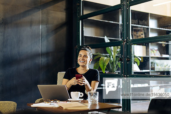 Happy casual young businesswoman with laptop and smartphone in loft office