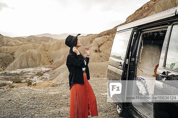 Junge Frau in Wüstenlandschaft neben einem Wohnmobil stehend  Almeria  Andalusien  Spanien