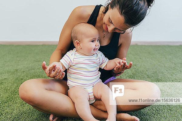 Junge Mutter und Baby beim Mutter-Kind-Turnen trainieren