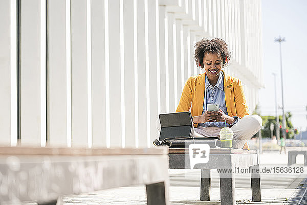 Lächelnde junge Frau mit Kopfhörer  Smartphone und Tablet in der Stadt