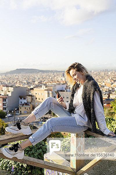 Junge Frau sitzt auf einem Geländer über der Stadt und telefoniert per Handy  Barcelona  Spanien
