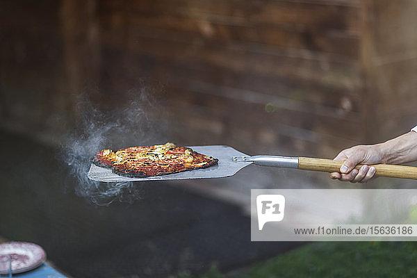 Abgehackte Hand einer Person  die auf einem Sommerfest gedämpfte Pizza mit Spachtel hält