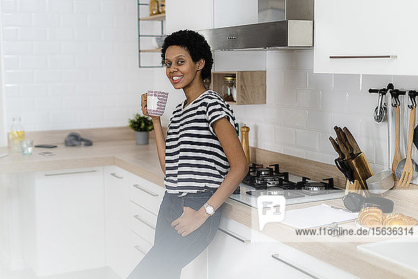 Portrait of smiling young woman holding mug in kitchen at home