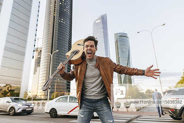 Portrait of screaming man with guitar in the city  Madrid  Spain