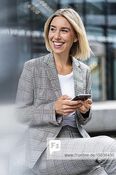 Glückliche junge Geschäftsfrau mit Mobiltelefon in der Stadt