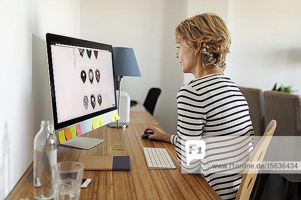 Mature woman using desktop at home
