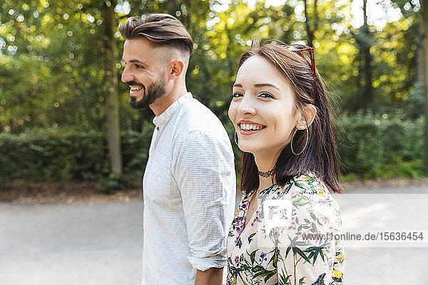 Porträt eines glücklichen jungen Paares beim Spaziergang in einem Park