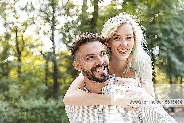 Porträt eines glücklichen jungen Mannes  der seine Freundin Huckepack nimmt