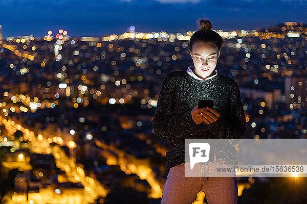 Junge Frau telefoniert nachts über der Stadt  Barcelona  Spanien