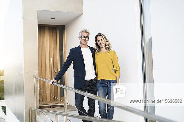 Porträt eines lächelnden Paares  das vor seinem modernen Zuhause steht