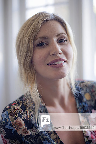 Portrait of blond woman sitting at home