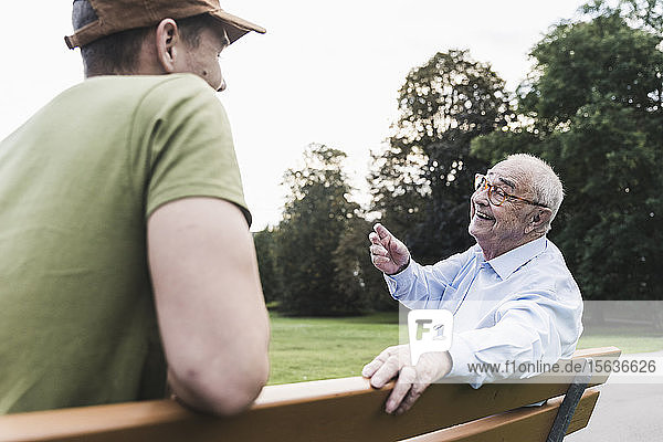 Happy senior man relaxing together with his grandson on a park bench