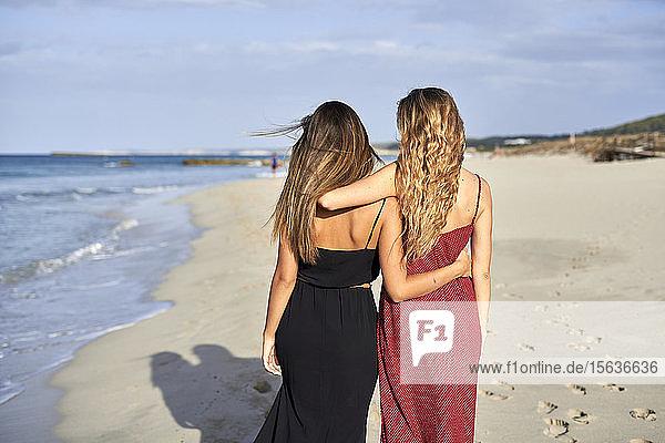 Zwei junge Frauen stehen Arm in Arm am Strand