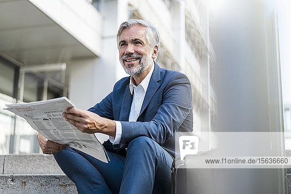 Lächelnder reifer Geschäftsmann sitzt mit Zeitung auf der Treppe in der Stadt