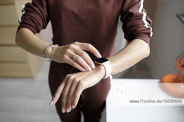 Frau tippt zu Hause auf intelligente Uhr