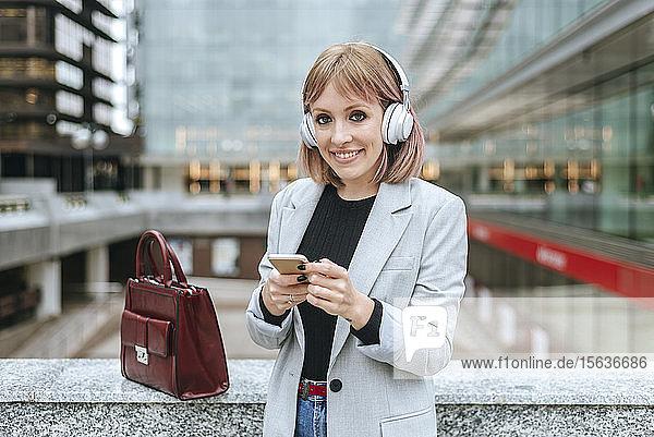 Lächelnde Frau imit Smartphone und Kopfhörern in der Stadt