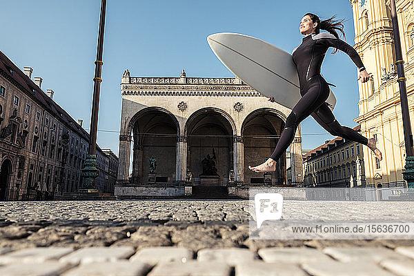 Junge Frau mit Surfbrett auf dem Weg nach Eisbach  München  Deutschland
