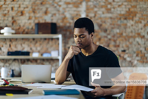 Young man sitting at table looking at notebook