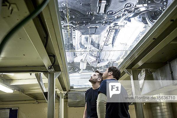 Zwei Kollegen in der Fabrik überprüfen Unterboden eines Autos