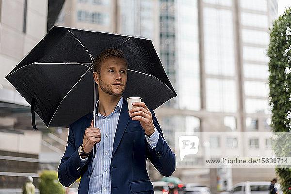 Junger Geschäftsmann mit Regenschirm trinkt an einem regnerischen Tag in Bangkok einen Kaffee