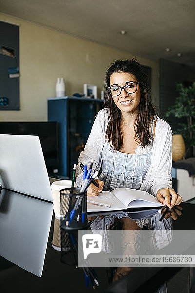 Portrait of smiling woman working on table at home