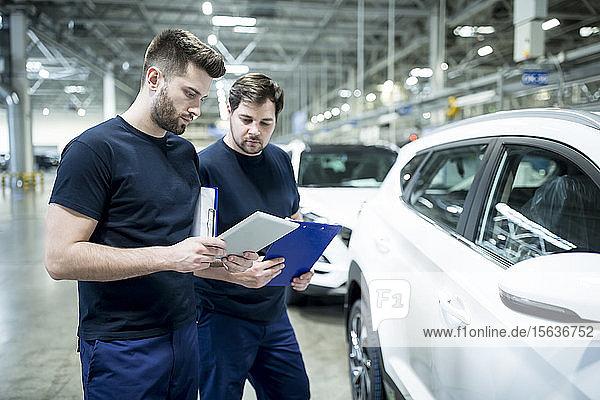 Zwei Kollegen arbeiten in einer modernen Autofabrik mit Zwischenablage und Tablett