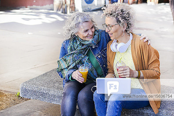 Senior mother with her adult daughter using laptop and drinking juices in the city