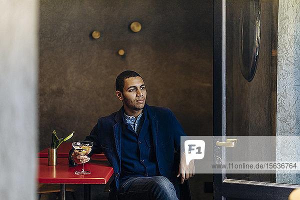 Junger Mann entspannt sich bei einem After-Work-Cocktail Junger Mann entspannt sich bei einem After-Work-Cocktail