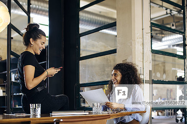 Two happy young businesswomen with smartphone in loft office