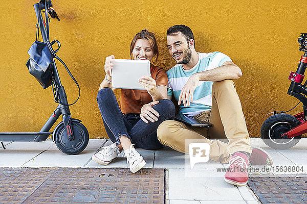 Porträt eines lächelnden Paares mit Elektrorollern mit digitalem Tablet