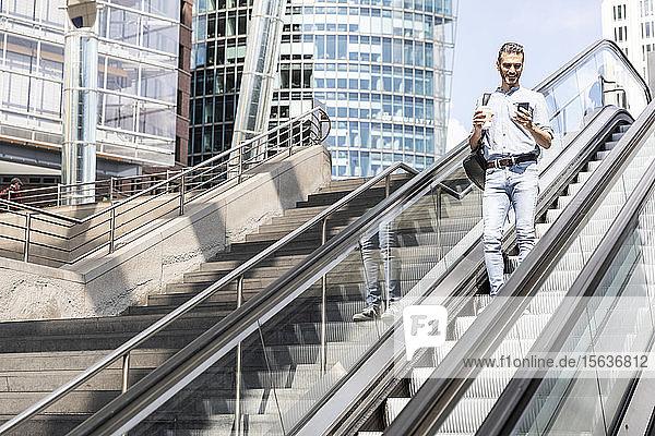 Lächelnder Geschäftsmann schaut auf das Smartphone auf der Rolltreppe in der Stadt  Berlin  Deutschland