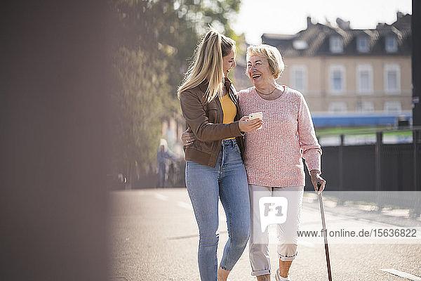 Enkelin und ihre Großmutter gehen auf einem Steg und benutzen ein Smartphone