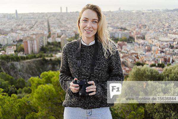 Porträt einer lächelnden jungen Frau mit Kamera bei Sonnenaufgang über der Stadt  Barcelona  Spanien