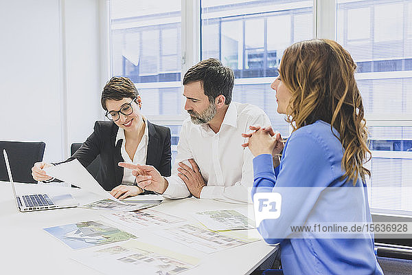 Geschäftsmann und zwei Geschäftsfrauen arbeiten gemeinsam am Schreibtisch im Büro