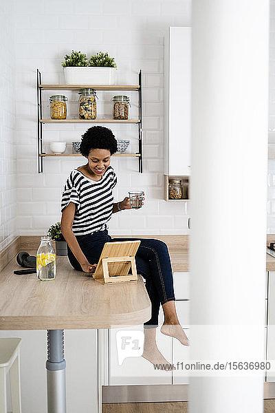 Junge Frau benutzt Tabletten und Trinkwasser in der Küche zu Hause