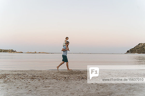 Father carrying daughter on shoulders on the beach at sunset