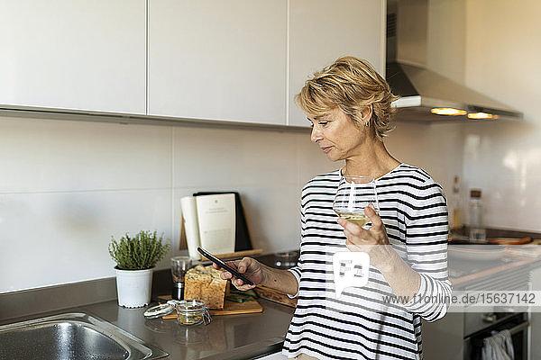 Reife Frau trinkt Wein und benutzt ihr Smartphone in der Küche zu Hause