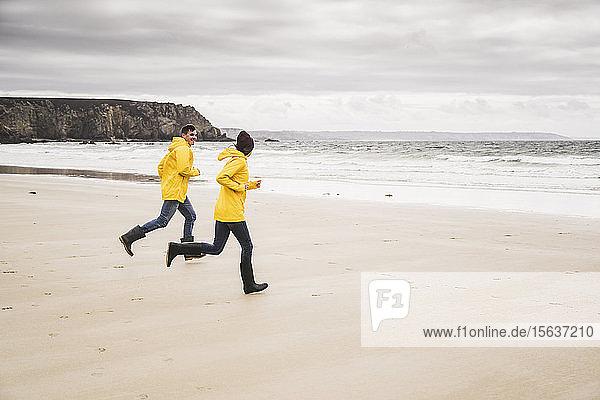 Junge Frau in gelben Regenjacken und beim Laufen am Strand  Bretagne  Frankreich