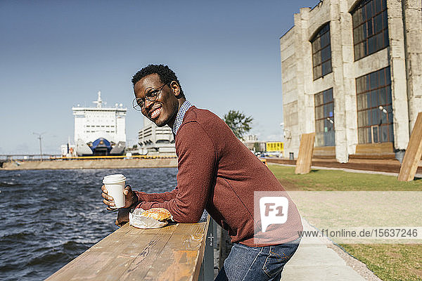 Young man looking at the sea  with eating hamburgerand coffee on railing