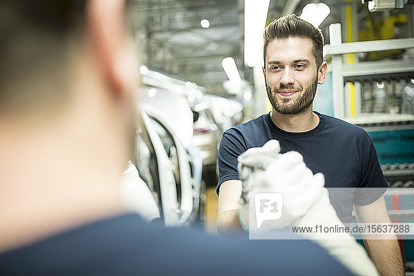 Zwei Kollegen schütteln sich in moderner Autofabrik die Hand