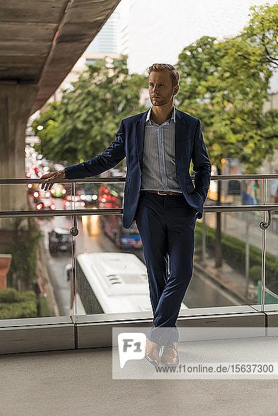 Junger Geschäftsmann auf der Fußgängerbrücke  seitwärts blickend