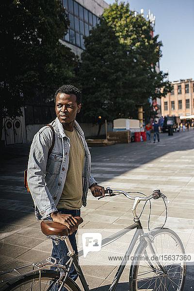 Zoung Mann pendelt in der Stadt  schiebt sein Fahrrad