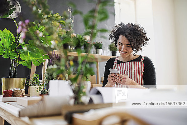 Smiling young woman using cell phone in a small shop with plants