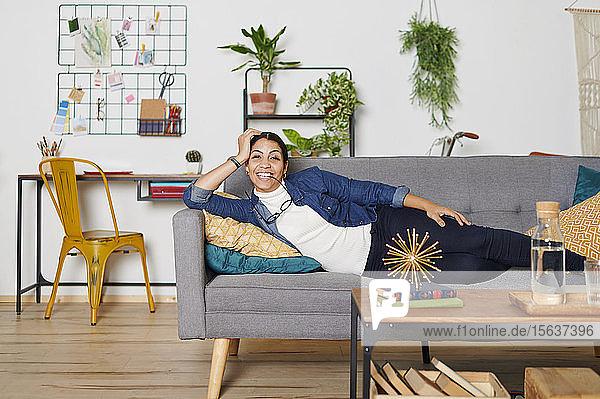Junge Frau ruht auf einer Couch im Wohnzimmer