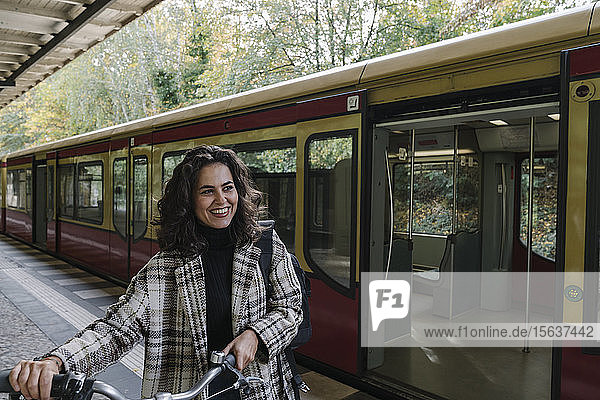 Happy woman with bicycle on an underground station platform  Berlin  Germany