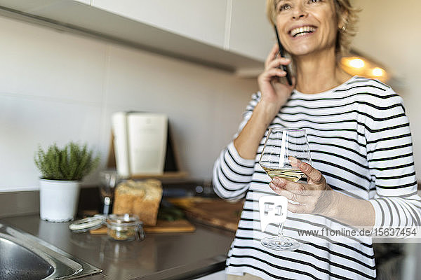 Happy mature woman drinking wine and talking on the phone in kitchen at home
